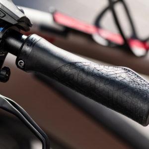 Ergonomiczne chwyty rowerowe na tle ramy rowerowej