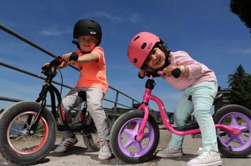 Dwójka dzieci w kaskach na rowerach dziecięcych
