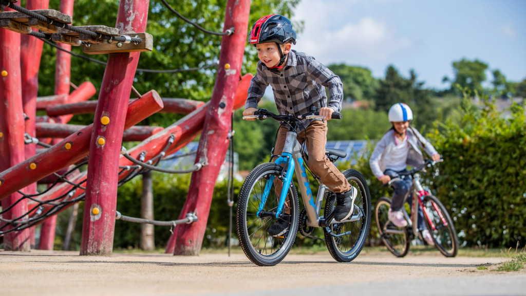 Dzieci na rowerach dziecięcych przejeżdżające obok placu zabaw